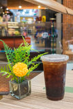 Cold coffee in glass with flower vase. On wooden table stock image