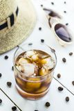 Cold coffee among summer accessories. Cold coffee in a glass with ice. On the table among coffee beans and summer women`s accessories. Summer relax concept Royalty Free Stock Image