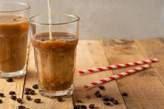 Cold coffee pouring in cream, milk in transparent glasses with ice and straws, on a wooden background, a cooling drink, refreshing.  stock photo