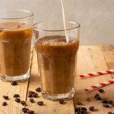 Cold coffee pouring in cream, milk in transparent glasses with ice and straws, on a wooden background, a cooling drink, refreshing.  royalty free stock images