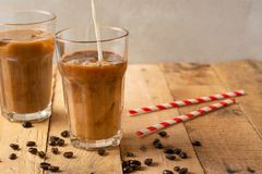Cold coffee pouring in cream, milk in transparent glasses with ice and straws, on a wooden background, a cooling drink, refreshing.  royalty free stock photos