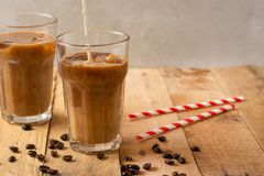 Cold coffee pouring in cream, milk in transparent glasses with ice and straws, on a wooden background, a cooling drink, refreshing.  stock images