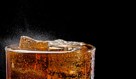 Cold cola with ice. Cold fizzing cola with ice on the black background Stock Image