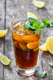 Cold cola with mint, lime and ice in glass on wooden background. Summer drinks and alcoholic cocktails.  stock photos