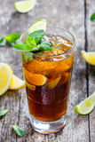 Cold cola with mint, lime and ice in glass on wooden background. Summer drinks and alcoholic cocktails Royalty Free Stock Images
