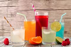 Cold colorful summer drinks against wood. Group of cold colorful summer drinks against a wooden background Royalty Free Stock Photography