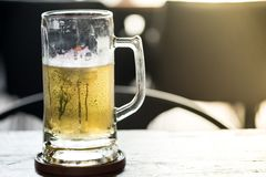Cold craft light and dark Beer in a glass. With water drops stock image