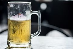 Cold craft light and dark Beer in a glass. With water drops royalty free stock photography