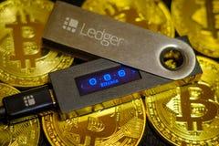 Cold crypto wallet Ledger Nano S lying on golden bitcoin coins. Moscow, Russia - September 8, 2017: Cold crypto wallet Ledger Nano S lying on golden bitcoin Stock Photos