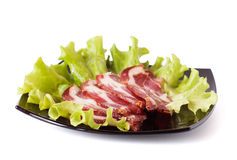 Cold cut: bacon, leaves on a plate Royalty Free Stock Photo