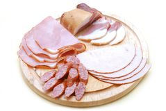 Cold cuts. Close-up of cold cuts on wood plate, isolated on white background Stock Image