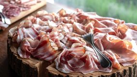 Cold cuts appetizer wooden chopping board tree trunk.  stock footage