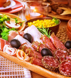 Cold cuts. Closeup on cold cuts in centerpiece of table, various of smoked meat, bacon, beef, ham, pepperoni, salamy, restaurant menu royalty free stock photography