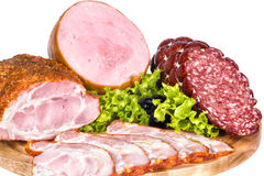 Cold cuts: ham, bacon, smoked sausage. Still life of sausages on a wooden cutting board Stock Images