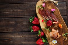 Cold cuts on a plain background, wooden board, strawberries and micro greens. Free place for text stock image