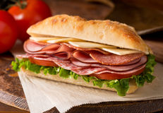 Cold Cuts Sandwich. A delicious sandwich with cold cuts, lettuce, tomato, and cheese on fresh ciabatta bread Royalty Free Stock Photos