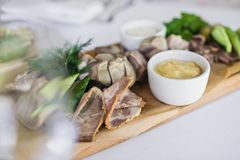 Cold cuts on a wooden chopping Board. Banquet at the restaurant. stock images