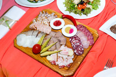 Cold cuts on wooden plate on banquet table Royalty Free Stock Photo