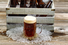 Cold dark beer in large glass mug with vintage crate with ice co Royalty Free Stock Photography