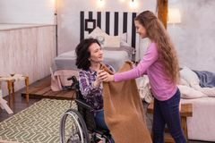 Attractive girl giving blanket to crippled woman. Cold day. Happy girl holding blanket while crippled women taking it Stock Photography