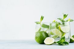Cold detox summer mineral water with lime, mint, ice, straw on soft white background, copy space. royalty free stock photo