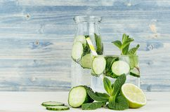 Cold detox water in glass and retro bottle with slices cucumber, mint, lime and straw on shabby light blue wood board. Royalty Free Stock Photos