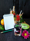 Cold detox water with organic berries and fruits and a notebook stock photography