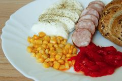 Cold dinner detail. Taken May 22, 2016 Jablonec nad Nisou Czech Republic cold supper on white plate mozzarella sliced sausage with bun corn and pickled peppers Stock Images