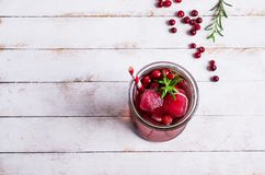 Cold drink with berries. And ice in glass on wooden background. Selective focus Royalty Free Stock Image