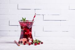Cold drink with berries. And ice in glass on wooden background. Selective focus Stock Photos
