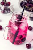 Cold Drink with Cherry in Jars on White Wooden Background Cold Detox Infused Water Summer Drink Vertical Toned royalty free stock photo