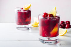 Cold drink with cherry and lemon in glasses, on white wooden background Stock Photo