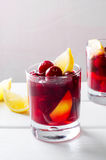 Cold drink with cherry and lemon in glasses, on white wooden background Stock Photography