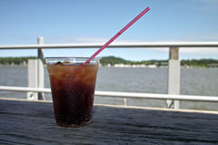 Cold Drink On A Dock. A cold soft drink on a rough wood table with a lake and shore line in the background Stock Photos