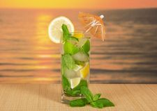 Cold drink with lemon slice against the sea sunset Royalty Free Stock Photography