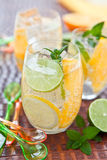 Cold drink with lemons and oranges Stock Photos