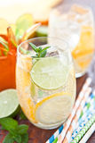 Cold drink with lemons and oranges Royalty Free Stock Images