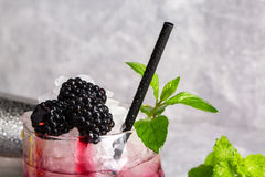Cold drink with mint and blackberries in a huge glass on a grey background, slice of lemon with berries and mint on a. Close-up of summer fresh cocktail with Stock Images
