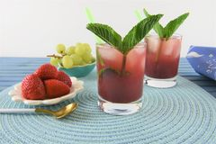 Cold drink in red berry and grape flavor. Glass of red fruit smoothie drink with ice and fresh mint leaf. Made with strawberry red and green grapes and plum stock image