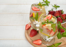Cold drink with strawberries, lemon and mint Royalty Free Stock Photos