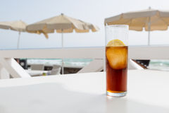 A cold drink on a terrace near the sea. A cold drink (cuba libre) with lemon and an ice cube on a white table on a terrace near the sea Stock Images