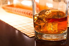 A cold drink. Transparent ice cubes in a glass of whiskey on the table Royalty Free Stock Images