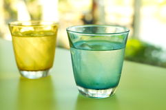 Cold drinking water in clear blue and yellow glass Royalty Free Stock Image