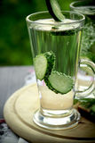 Cold drinking water in a glass with a cucumber on a wooden board. Cold drinking water with cucumber  in a glass Stock Photos