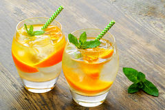 Cold drinks with ice and mint. Orange cocktail on stock photos