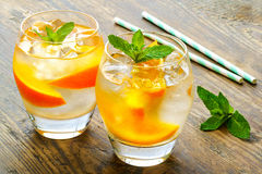 Cold drinks with ice and mint. Orange cocktail on Stock Images