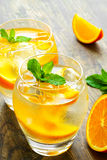 Cold drinks with ice and mint. Orange cocktail on Royalty Free Stock Image