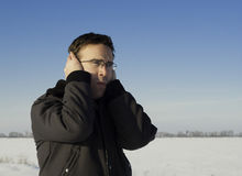 Cold Ears. A young man standing outside in the winter, holding his ears to keep them warm Stock Photos