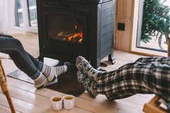 Closeup photo of human feet in warm woolen socks over fire place. Cold fall or winter day. People drinking tea and resting by the stove. Closeup photo of human royalty free stock photo