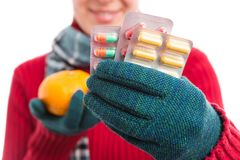 Cold female showing pills versus natural vitamins concept. Cold young female showing pills versus natural vitamins concept stock image
